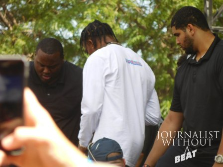 Travis Scott being escorted off the stage by security