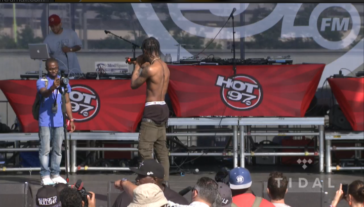 Travi$ Scott kicking a photographer off stage.